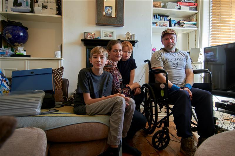 Anthony and his family sitting in the front room of their privately rented home