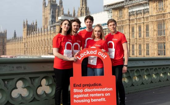 "Group of Shelter campaigners standing in front of parliament holding a large cardboard padlock with ""Locked Out"" written on it"