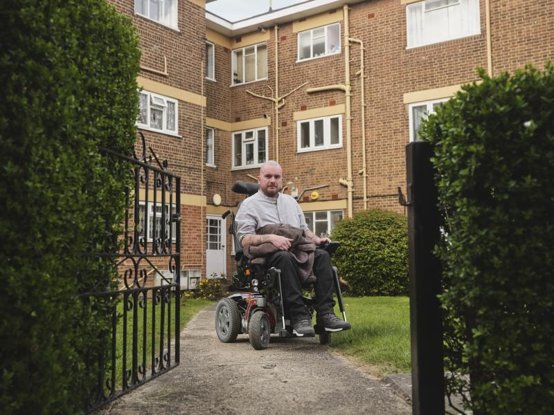 Stephen, a wheelchair user and housing campaigner, outside their home